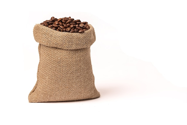 Roasted brown coffee beans. in a burlap sack. on white background. close-up.