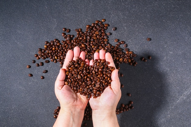 Roasted brown coffee beans on a gray background