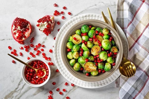芽キャベツのロースト、ザクロの種と白い大理石の石の背景に金色のカトラリーと白いプレートで提供される健康的なベジタリアン料理、クローズアップ、上面図
