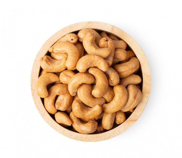 Roasted cashew nuts with salt in wood bowl isolated