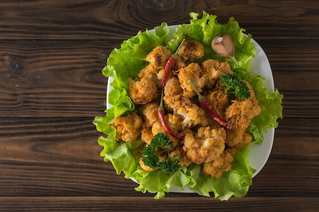 Roasted cauliflower inflorescences with pepper on lettuce leaves. vegetarian cauliflower appetizer. flat lay.