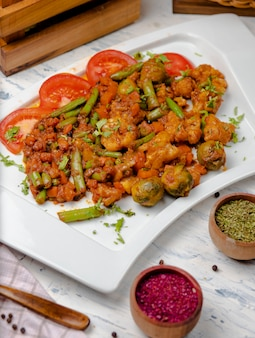 Roasted cauliflower with sprouts, beans and served with tomato sauce and herbs.