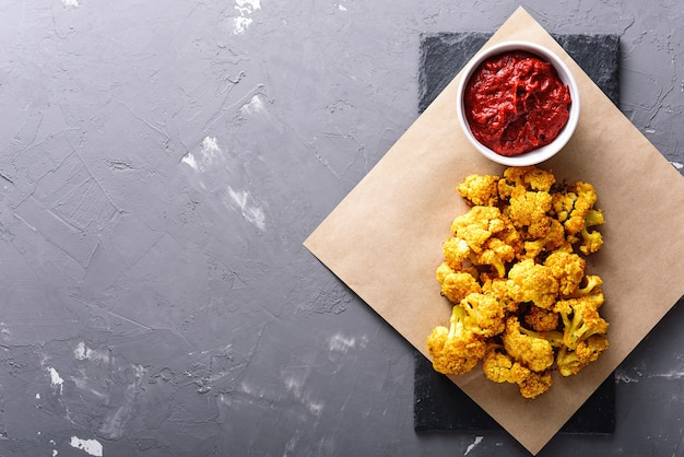 Roasted cauliflower with tomato sauce on grey background with copy space