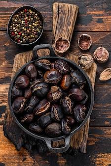 焼き栗を木製のまな板の上で鍋に盛り付けます。木製の背景。上面図。