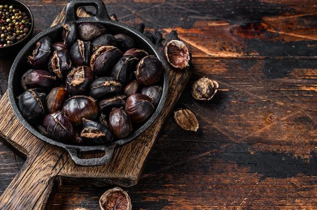 焼き栗を木製のまな板の上で鍋に盛り付けます。木製のテーブル。上面図。