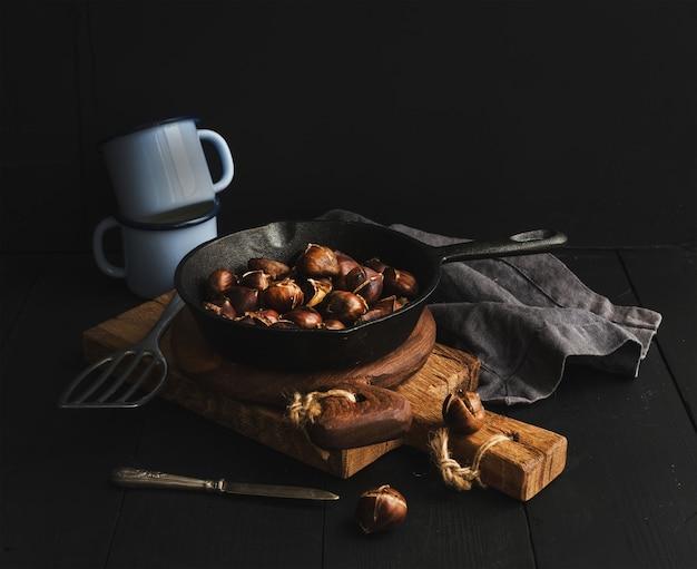 Roasted chestnuts in skillet cooking pan over rusti wooden boards, blue enamel mugs, towel on dark