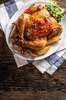 Жареный цыпленок и американский картофель с перцем чили и зеленью - вид сверху.
