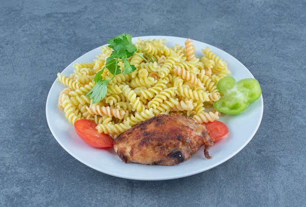 Жареный цыпленок и фузилли на белой тарелке.