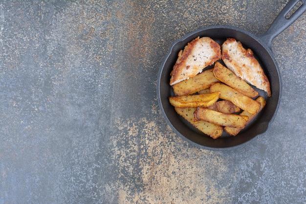 Жареный цыпленок и картофель на черной сковороде. фото высокого качества