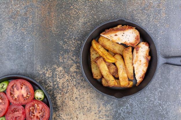 Жареный цыпленок и картофель на сковороде с овощной тарелкой. фото высокого качества