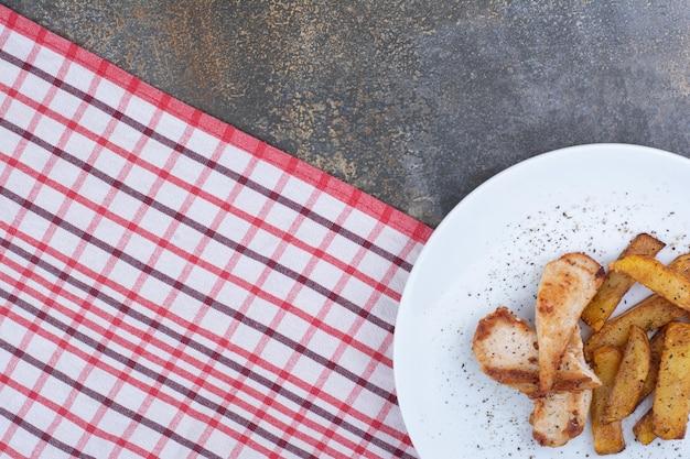 Жареный цыпленок и картофель на белой тарелке. фото высокого качества