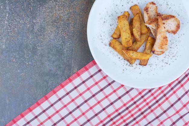 Жареный цыпленок и картофель на белой тарелке со скатертью. фото высокого качества
