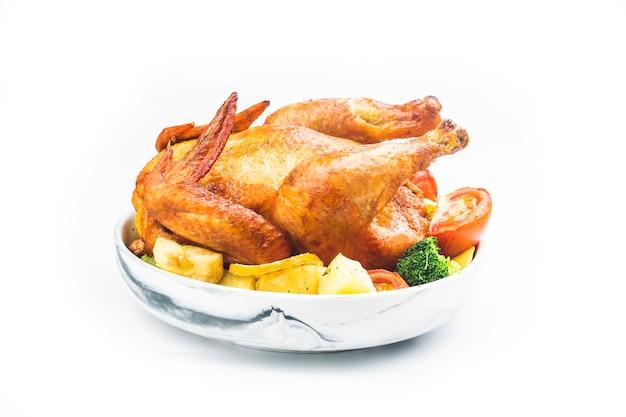 Жареный цыпленок и картофель на белой тарелке