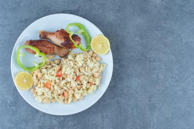Жареный цыпленок и рис с нутом на белой тарелке.