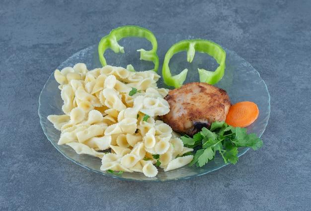 Жареный цыпленок и вкусные макароны на стеклянной тарелке.