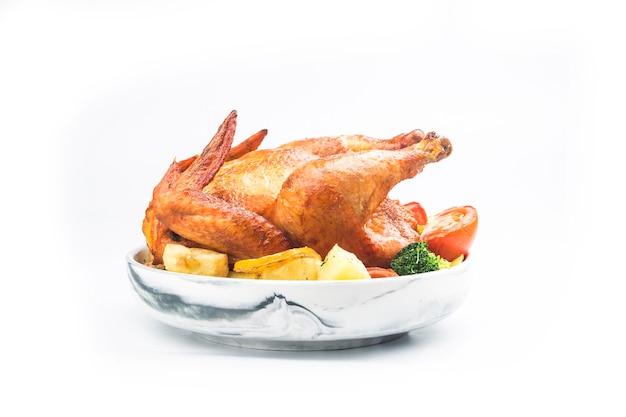 白いテーブルの上のローストチキンと野菜