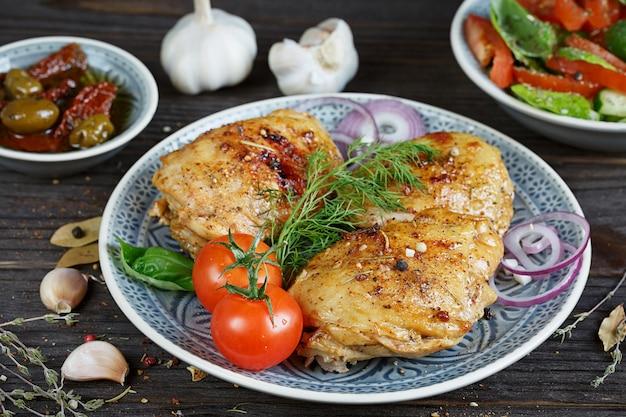 Жареный цыпленок и овощи на деревянных фоне