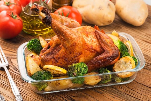 나무 테이블에 구운 된 닭고기와 야채