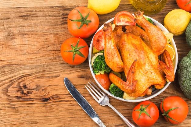 Жареный цыпленок и овощи на деревянном столе