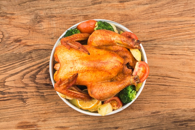 나무 테이블에 구운 닭고기와 야채