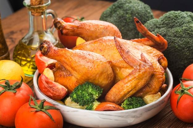 木製のテーブルでローストチキンと野菜
