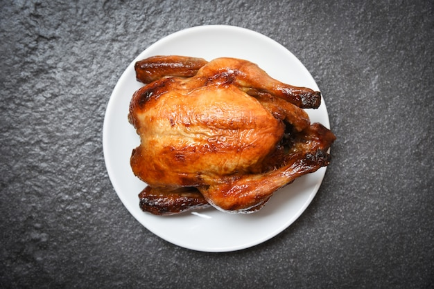 Roasted chicken / baked whole chicken grilled on white plate and dark background on top view