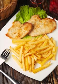 Кусочки жареной куриной грудки с картофелем фри в белой тарелке.