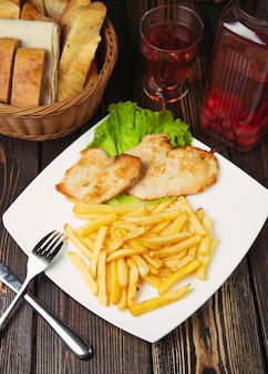 Roasted chicken breast nuggets with french fries in white plate.
