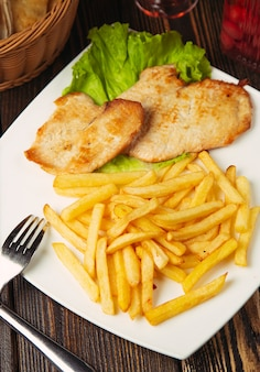 Roasted chicken breast nuggets with french fries in white plate