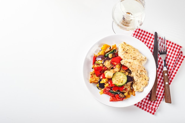 Roasted chicken breast with grilled zucchini, eggplant and red and yellow bell peppers on white plate with wine glass. top view. place for text.