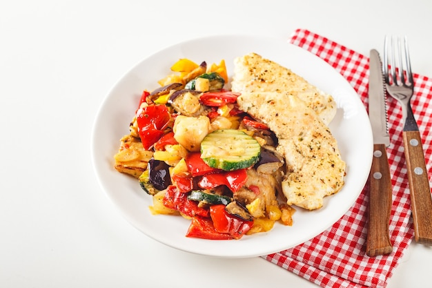 Roasted chicken breast with grilled zucchini, eggplant and red and yellow bell peppers on white plate with wine glass.