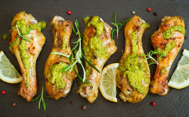 Roasted chicken drumstick in green sauce with lemon