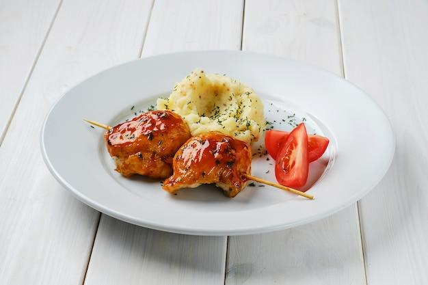 Жареное куриное филе на шпажке с соусом барбекю и картофельным пюре на белом деревянном столе
