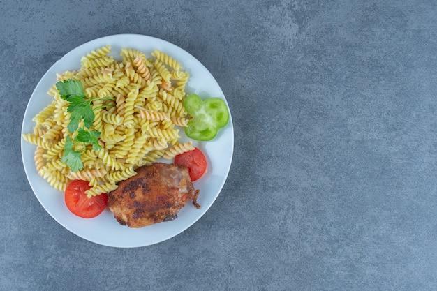 Pollo arrosto e fusilli sul piatto bianco.