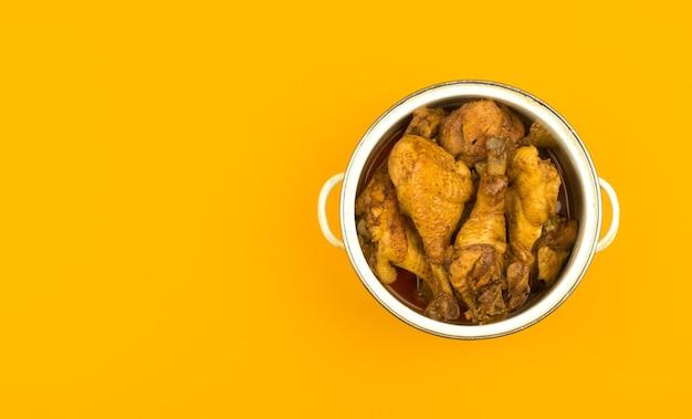 냄비에 구운 닭고기, 노란색 및 주황색 주방 평평한 배경, 복사 공간 및 위쪽 전망 사진