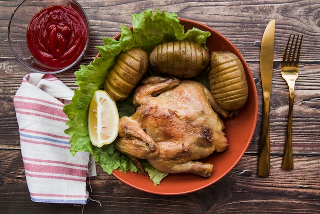 Жареная курица в миске с картофелем; нож; салфетка; лимон; соус и вилка на столе