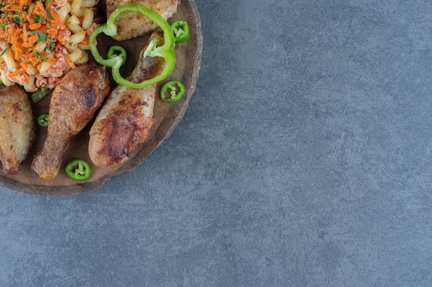 Cosce di pollo arrosto e pasta su un pezzo di legno.