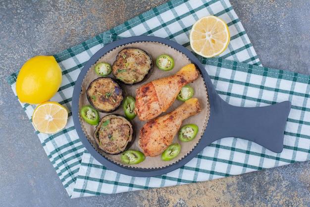 어두운 보드에 튀긴 야채와 레몬 구운 닭 다리. 고품질 사진