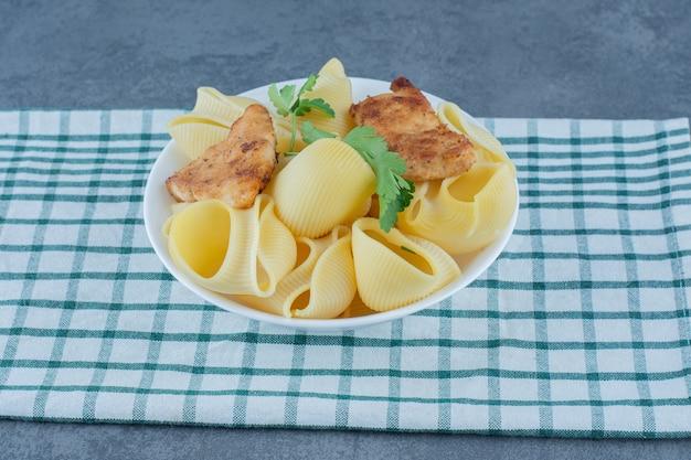 Pepite di pollo arrosto e pasta bollita in una ciotola bianca.