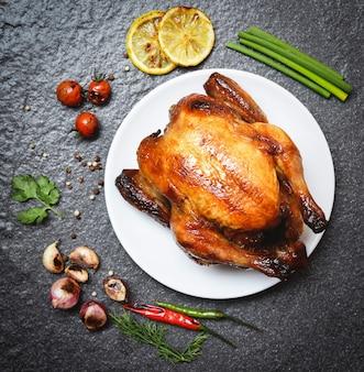 Жареная курица на тарелке - запеченная целая курица на гриле с зеленью и специями