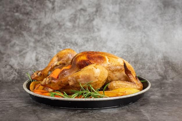 회색 접시에 구운 닭고기, 감자, 야채. 측면보기.