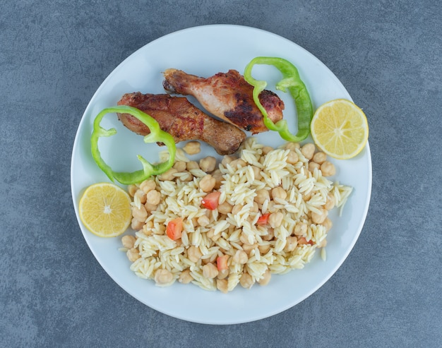 Roasted chicken and rice with chickpeas on white plate.