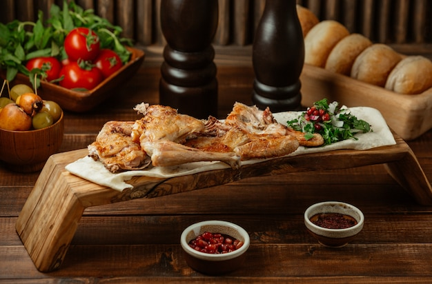 Roasted chicken served with herbs on a bamboo platter
