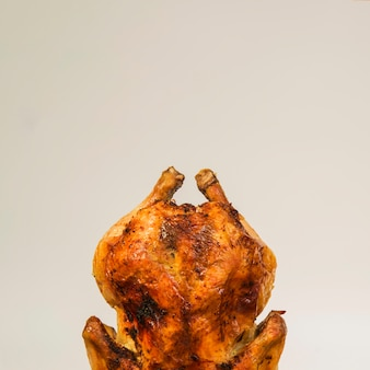 Roasted chicken standing on white background