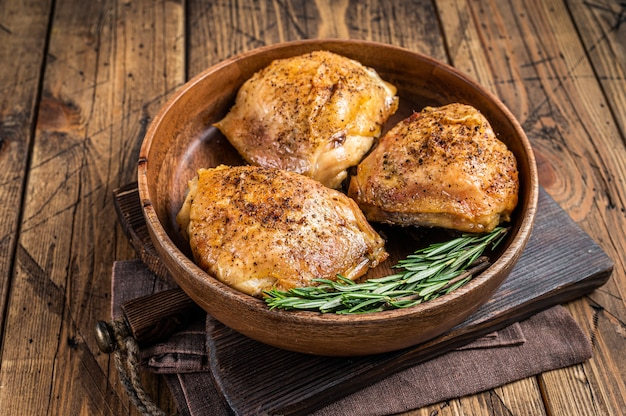 Жареные куриные бедра в деревянной тарелке с розмарином и зеленью. деревянный фон. вид сверху.