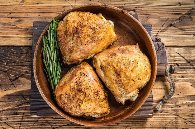 Жареные куриные бедра в деревянной тарелке с розмарином и зеленью