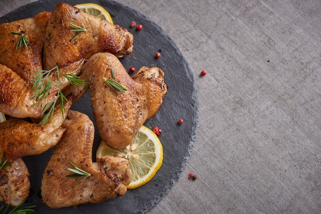 Ali di pollo arrosto in salsa barbecue con semi di pepe rosmarino, sale in una lastra di pietra nera su un tavolo di pietra grigia.