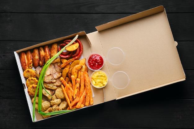 Жареные куриные крылышки, палочки из сельдерея и моркови и соус в картонной коробке