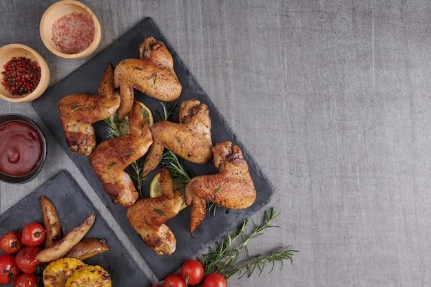 Жареные куриные крылышки в соусе барбекю и смешанный овощной салат с перцем, розмарином, солью в черной каменной тарелке на сером каменном столе.