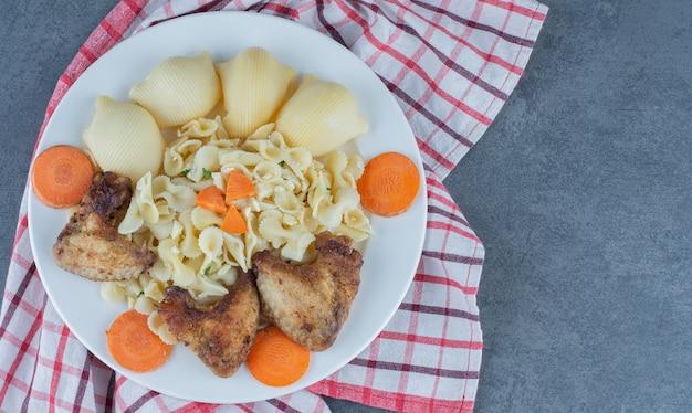 Ali di pollo arrosto e pasta sul piatto bianco.